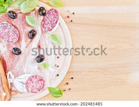 Ham,salami, olive and basil on wood - stock photo
