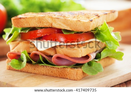 ham sandwich on wooden board