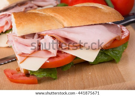 Ham sandwich with cheese, tomato and lettuce on a baguette