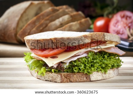 Ham sandwich with salad and cheese.  Loaf of bread behind. - stock photo