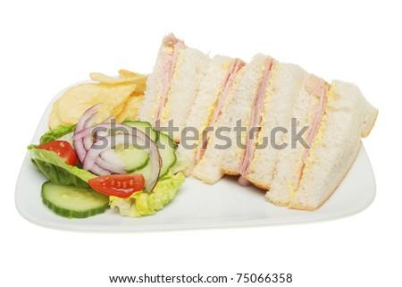 Ham sandwich with salad garnish and potato crisps on a plate - stock photo