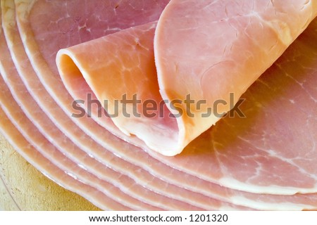 Ham slices on wooden board, with top slice folded - stock photo
