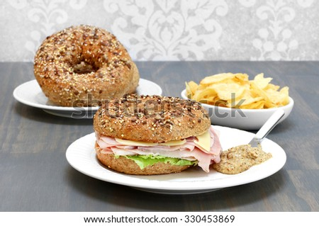 Ham, swiss cheese and lettuce sandwich on a multi grain and seed bagel with a side of spicy mustard.