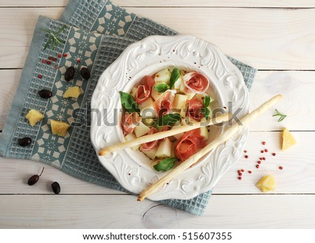 ham with melon and breadsticks on a plate, olives and Parmesan cheese on wooden background - top view