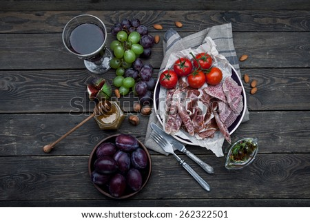 Ham with tomatoes, plums and nuts on wooden background - stock photo