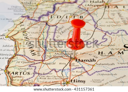 Hama (Hamah) marked on map with red pushpin. Selective focus on the word Hamah and the pushpin. Pin is in an angle. Midground is sharp while foreground and background is blurry. - stock photo