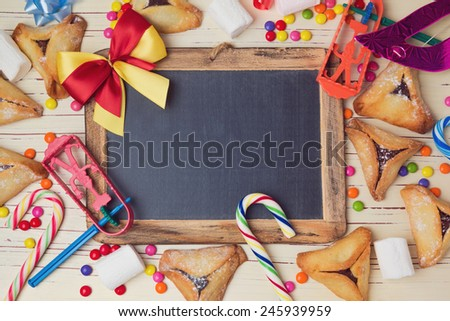 Hamantaschen cookies and chalkboard on wooden white table. View from above - stock photo