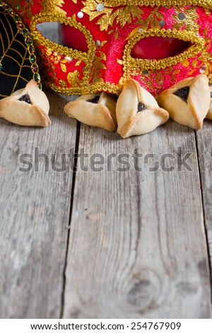 Hamantaschen cookies or Haman's ears and carnival masks for Purim celebration (jewish holiday). Copy space background. - stock photo