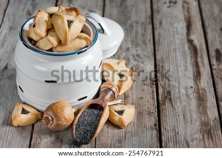 Hamantaschen cookies or Haman's ears - triangle cookies stuffed with poppy seeds, traditioal food on Purim, judaic holiday. Copy space background. - stock photo