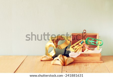 Hamantaschen cookies or hamans ears and mask for Purim celebration (jewish holiday). retro filtered image  - stock photo