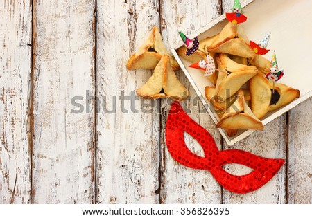 Hamantaschen cookies or hamans ears and  red mask Purim celebration (jewish carnival holiday). selective focus  - stock photo