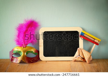 Hamantaschen cookies or hamans ears, gragger and mask for Purim celebration (jewish holiday)  - stock photo
