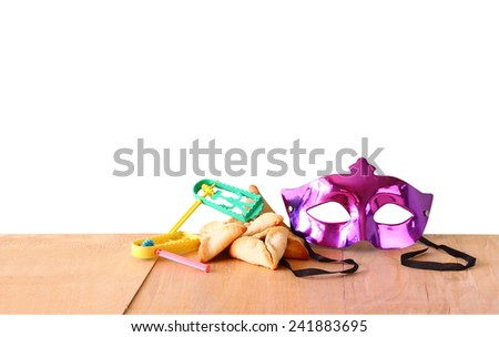 Hamantaschen cookies or hamans ears, noisemaker and mask for Purim celebration (jewish holiday) with isolated background  - stock photo
