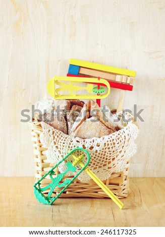 Hamantaschen cookies or hamans ears Purim celebration and gragger (jewish holiday)  - stock photo