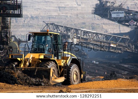 HAMBACH, GERMANY - SEPTEMBER 1: A power shovel and one of the world's largest bucket-wheel excavators digging coal in one of the world's deepest open-pit mines in Hambach on September 1, 2010 - stock photo