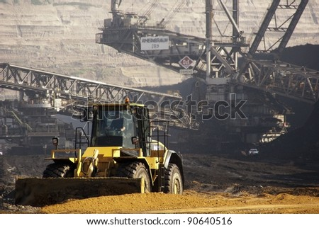 HAMBACH, GERMANY - SEPTEMBER 1, 2010: A shovel and one of the world's largest excavators digging lignite (brown-coal) in one of the deepest open-pit mines in Hambach, Germany on September 1, 2010. - stock photo