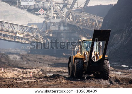HAMBACH, GERMANY - SEPTEMBER 1: Power-shovels and one of the world's largest excavators (background) digging lignite in of the world's deepest open-pit mines in Hambach on September 1, 2010. - stock photo