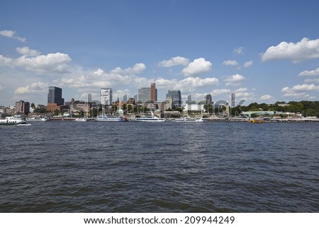 HAMBURG, GERMANY - AUGUST, 8. The skyline of the Harbor of Hamburg taken at bright sunlight with blue sky and white clouds on August 8, 2014.