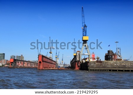 Hamburg, Germany - famous port seen from river Elbe. Industrial harbor cranes. - stock photo