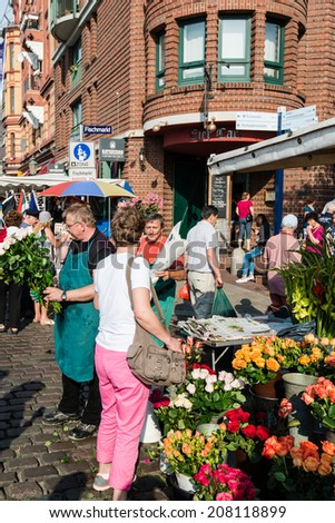 Hamburg, Germany - July 20, 2014: A florist is selling flowers on the traditional Hamburg Fish Market in the early Sunday Morning on July 20, 2014 in Hamburg, Germany. The Fish Market is active since - stock photo