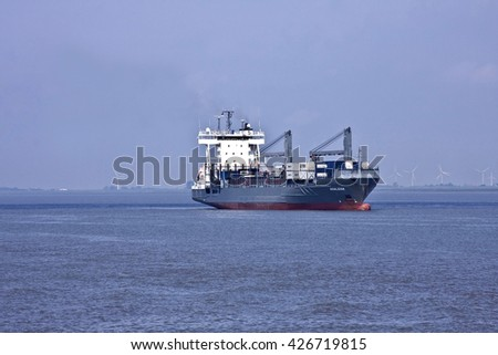 HAMBURG, GERMANY - JUNE 19, 2016:Container ship or multi-role vessel on the Elbe to Hamburg, at Brunsbüttel, Lower Saxony, Germany, Europe