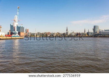 HAMBURG, GERMANY - MAY 06. Gantry crane at the quay in the south west harbor basin in Hamburg district Kleiner Grasbrook on May 06, 2015. In the background the HafenCity with the Elbphilharmonie - stock photo
