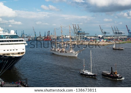 HAMBURG, GERMANY - MAY 12, 2013: The Mein Schiff 1 luxury cruise ship is passed by several classic ships during the 824th Hamburg Harbour Anniversary on May 12, 2013 in Hamburg, Germany.