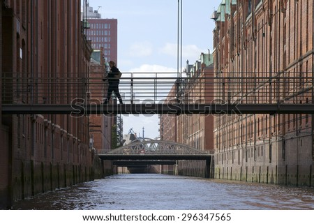 HAMBURG, GERMANY - SEPTEMBER 22: A woman crosses a bridge over a canal in Hamburg's warehouse district on September 22, 2014 in Hamburg / City of warehouses Hamburg   - stock photo