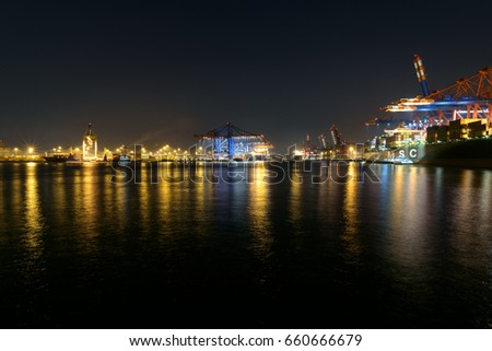 HAMBURG, HARBOR, GERMANY - Mai 20, 2017. Industrial port at night. The Elbe with Harbor crane and freight ships on the eurogate and burchardkai, International ships loading and unloading.