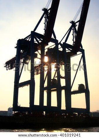 Hamburg Harbor in the sunrise or sunset. Freight shipping cranes. - stock photo