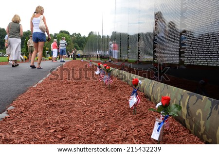 HAMBURG, MI - AUGUST 30: Visitors walk past the traveling Moving Wall Vietnam War memorial exhibit in Hamburg, MI on August 30, 2014. - stock photo