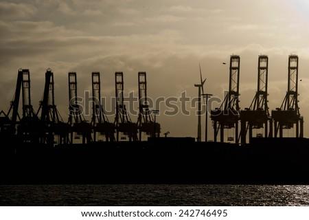 hamburg port crane silhouette at sunset - stock photo