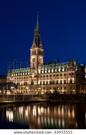 Hamburg Rathaus (city hall) in Germany at night. Part of the building is reflected in the Small Alster, a channelized part of the river Alster. - stock photo