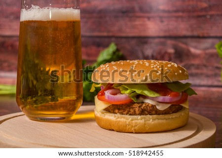 Hamburger and beer on wooden board