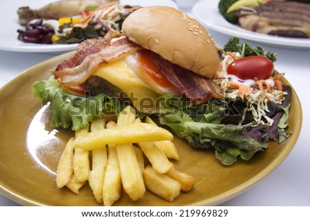 hamburger beef bacon egg french fries and salad  - stock photo