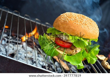 Hamburger - burger with grilled beef, cheese and vegetables on flame bbq - stock photo
