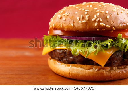 Hamburger closeup on red background with copyspace - stock photo