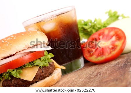 hamburger, drink,tomato,lettuce over cutting board wooden - stock photo