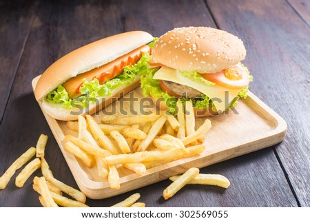 hamburger, hot dog, french fries on the wooden background - stock photo