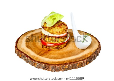 Hamburger made from potato pancakes, greens and vegetables on wooden board. Isolated on white background.