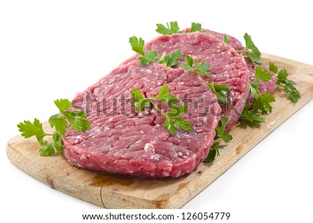Hamburger of beef on wooden board with parsley - stock photo