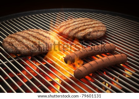 Hamburger patties and hot dogs on the grill under flaming coals - stock photo