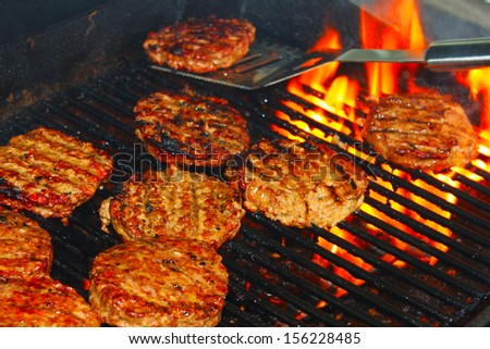 Hamburger patties on a grill - stock photo