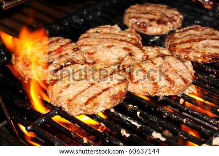 Hamburger patties on a grill - stock photo