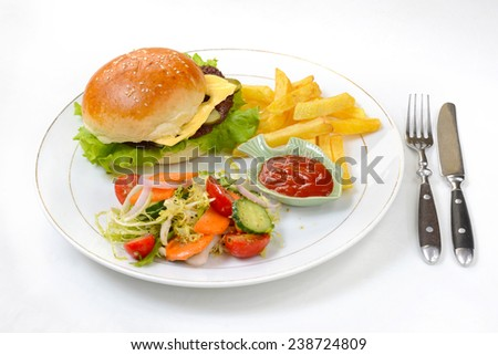 Hamburger served with fries and salad - stock photo