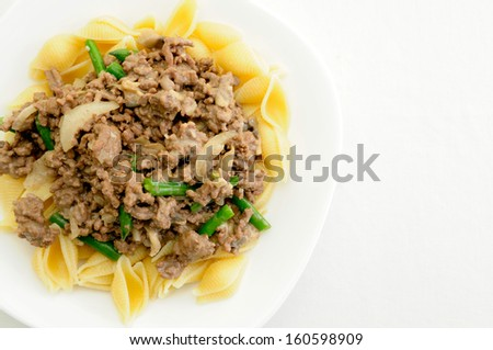 hamburger stroganoff with green beans over shell pasta - stock photo