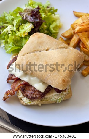 Hamburger with bacon and beef, french fries and green salad
