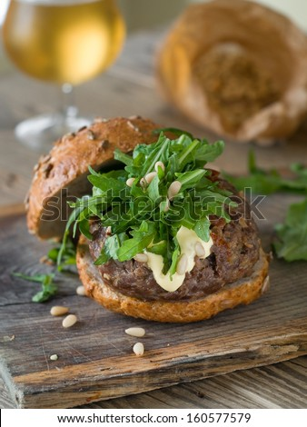 Hamburger with burger,  arugula and pine nuts, selective focus  - stock photo