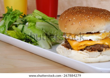 Hamburger with cheese and egg, side salad and ketchup bottles - stock photo