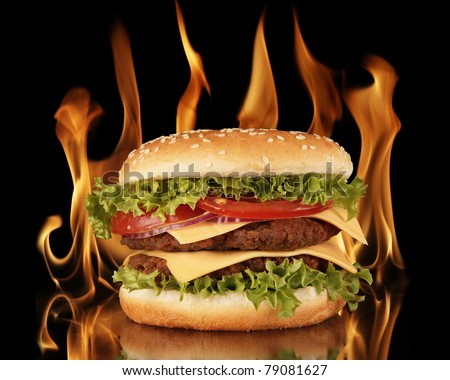 Hamburger with fire on black background - stock photo